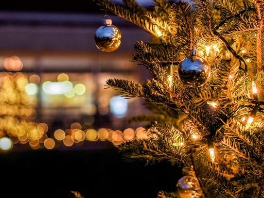 A Christmas tree is lit with string lights and ornaments.