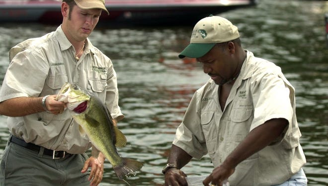 Logan Sherrer, left, and Mike Reagan bag one of their catch as they prepare for the weigh-in at the 2005 All-City Bass Tournament at Cross Lake.