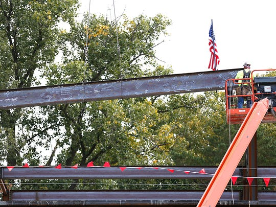 A steel beam, signed with hundreds of past and present students and faculty of St. Mary's Springs Academy, is fitted into the new construction of the school Wednesday afternoon. Wednesday September 30, 2015.