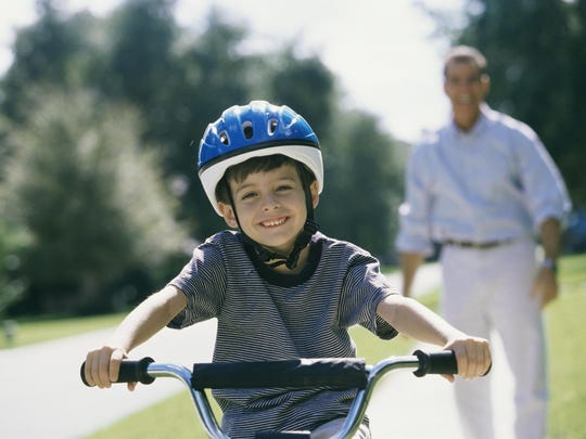 Boy (6-7) cycling, father standing behind him