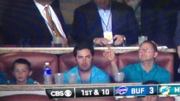 Astorino (right) seen on camera at the Sun Life Stadium suite in Miami for a game between the Buffalo Bills and Miami Dolphins with his 11-year-old son Sean and campaign manager Michael Lawler.