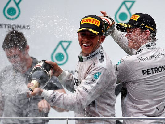 Mercedes driver Lewis Hamilton of Britain sprays champagne on the podium with teammate Nico Rosberg, right, after winning the the Malaysian Formula One Grand Prix at Sepang International Circuit in Sepang, Malaysia, Sunday, March 30, 2014. Rosberg finished in second place. (AP Photo/Vincent Thian)