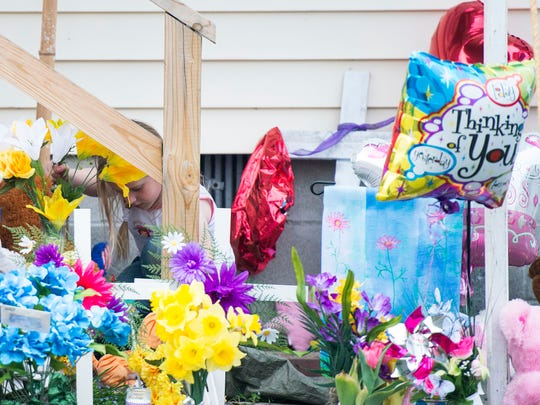 A young girl places flowers at a memorial site at the Todd residence before a prayer vigil Friday night, April 10 in Princess Anne.