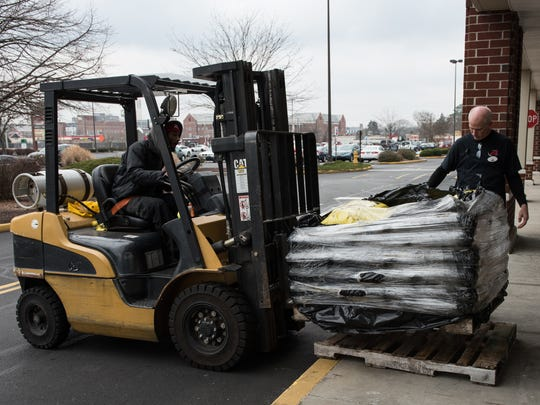Two employees from Rommel's Ace Home Center unload a pallet of rock salt on Friday, Jan. 6, 2017.