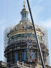 Scaffolding wraps around the dome of the Iowa Capitol building, Wednesday, Aug. 9, 2017, in Des Moines, Iowa. About two dozen workers are spending a hot summer on scaffolding that wraps around Iowa's 131-year-old Capitol. The priority is replacing 15,000 bricks that have deteriorated in the interior dome, but because that task required construction of scaffolding that climbs about 75-feet up from the main structure, maintenance officials decided it was the perfect time to make other repairs to the building.