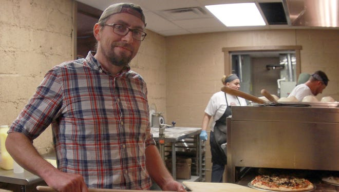 Prince Street Pizza and Pub co-owner Spencer Wakefield cooks a pizza during the business' opening Jan. 8.