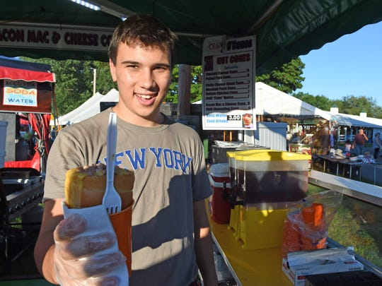 Max Ickes, of Rhinebeck, serves up a conesandwich full of macaroni and cheese with bacon during the opening day of the Ulster County Fair on Tuesday.
