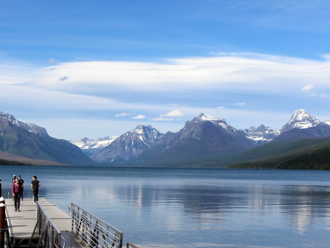 Snow-capped mountains reflect in Lake McDonald in Glazier