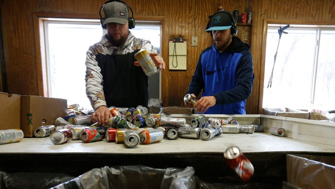 Josh Thompson, left, and Ben Allen sort through a bag of aluminum cans on March 16, 2017, at the Kans R Us redemption center in Perry.