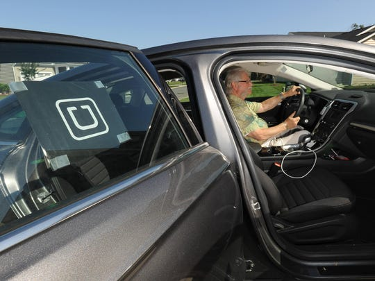 A logo for the ride-hailing service Uber is affixed to the window of Harris Marx's vehicle. Marx said police in Dewey Beach have told him he needs a business license.