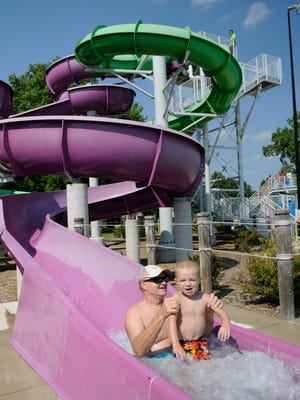Swimmers enjoy a water slide at Resch Aquatic Center in Green Bay.