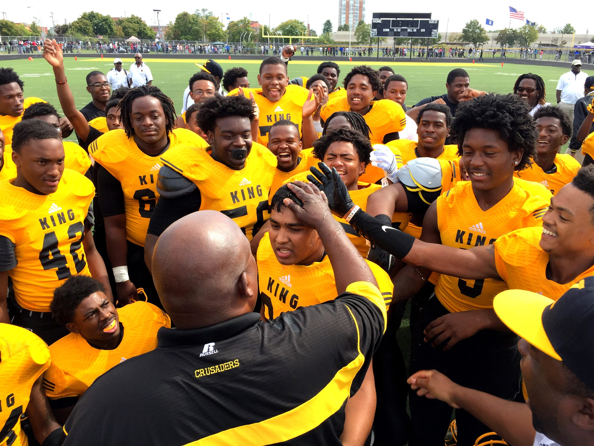 Detroit King football coach Dale Harvel, foreground, congratulates his team after beating Detroit Cass Tech on Sept. 26, 2015.