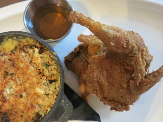 Crispy buttermilk-fried quail from Manchester Farms is served at Detroit's Central Kitchen + Bar with creamed sweet-corn gratin and a container of lavender honey, in which to dip savory bites of the quail. Photo 8/18/15 by Sylvia Rector Detroit Free Press