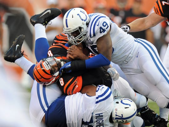 Colts linebacker Caesar Rayford, #49, and teammate Montori Hughes sandwich Bengals quarterback Josh Johnson in the first half of Thursday night's game against the Bengals at One Paul Brown Stadium in Cincinnati on August 29, 2013.