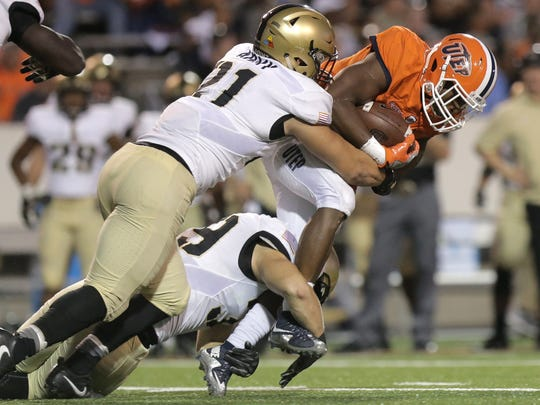 UTEP running back Aaron Jones is taken down by a pair of Army defenders Saturday at the Sun Bowl.