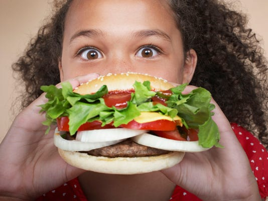 Young girl indoors eating a hamburger