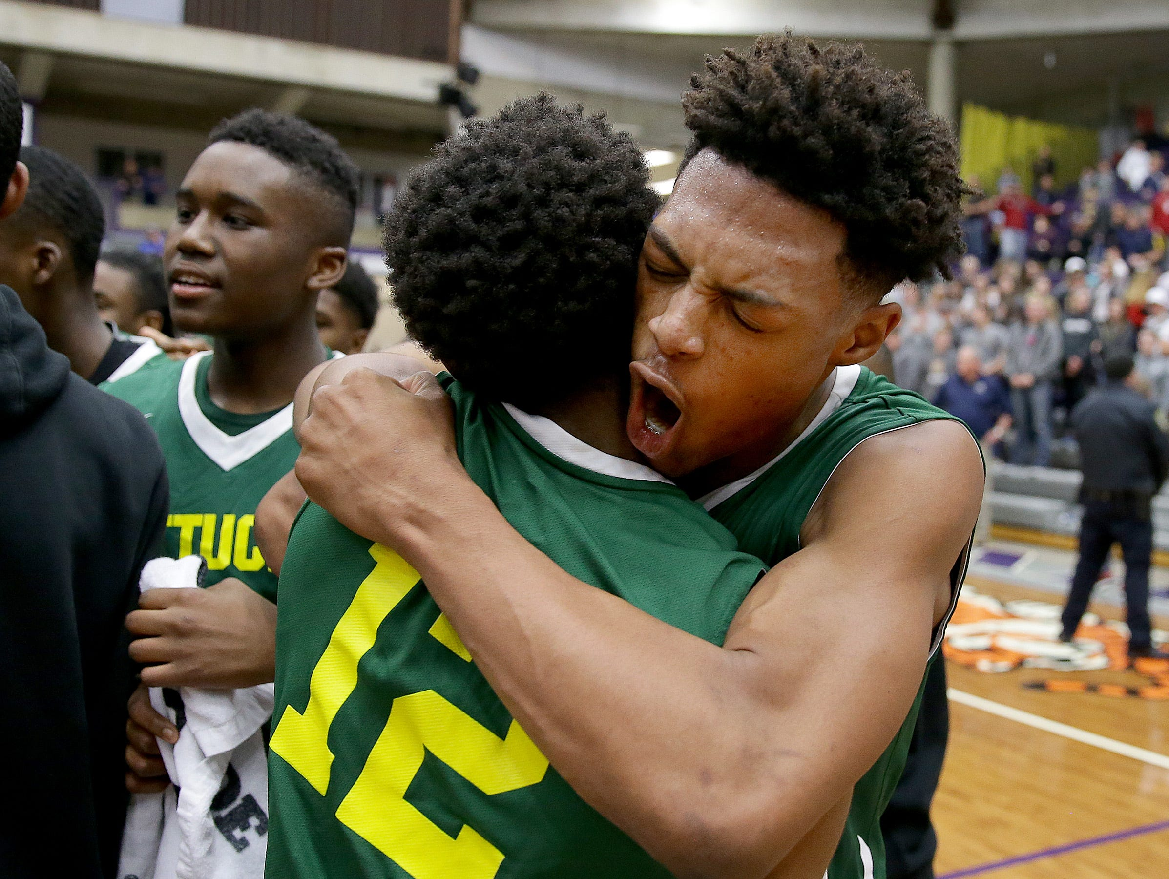 Attuck' Nike Sibande (22) hugs Zac Owens (12) following their win in the IHSAA Boys Regional championship game Saturday at the McAnally Center in Greencastle.