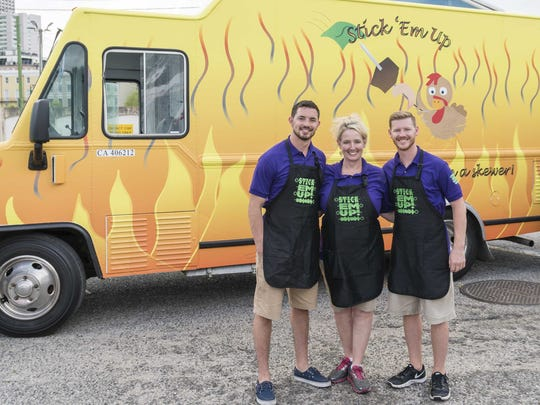 "Rogersville natives Justin, Shona and Landon House stand in front of their food truck, Stick 'Em Up. They will compete on the Food Network show ""The Great Food Truck Race: Battle for the South."""