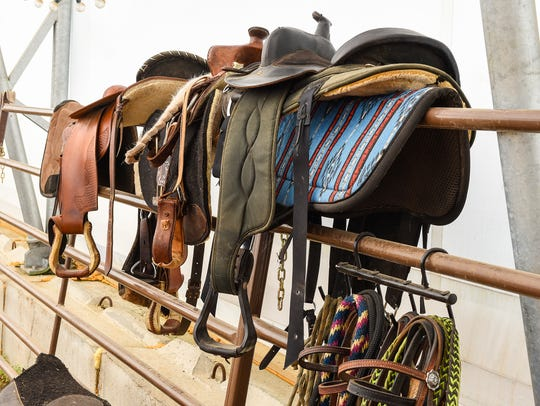 Saddles and equipment are ready in the riding arena