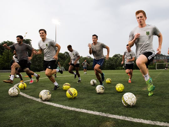 Greenville FC players run through warm-up drills during