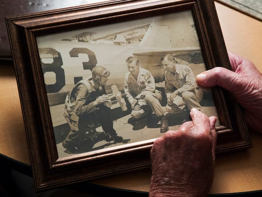Walter Kaslikowski, 95, admires a picture of his brothers Ted, left, Jack and Stanley. The Kaslikowski brothers served in World War II.