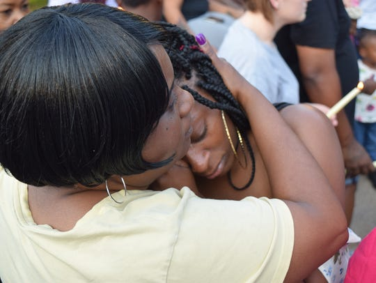 James Taylor's sister hugs an attendee of a vigil on