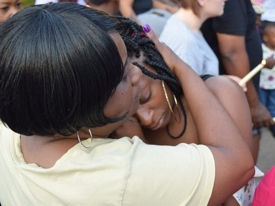 James Taylor's sister hugs an attendee of a vigil on May 16, 2017. Friends and family members gathered to honor Taylor, who was one of two men killed in a shooting in North Knoxville the day before.