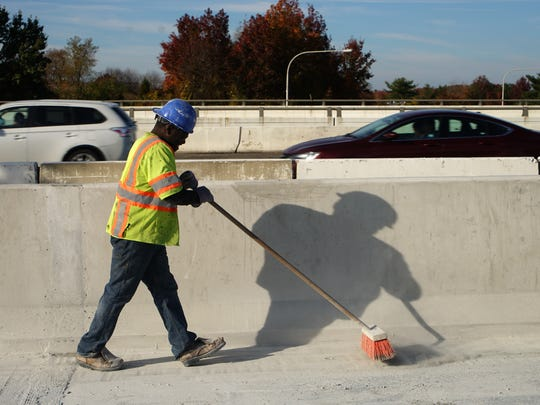 James Jones, with Mumford & Miller Concrete, sweeps away concrete dust as worker grind the deck for resurfacing the middle lanes of  I-95 south of the Route 1 overpass.