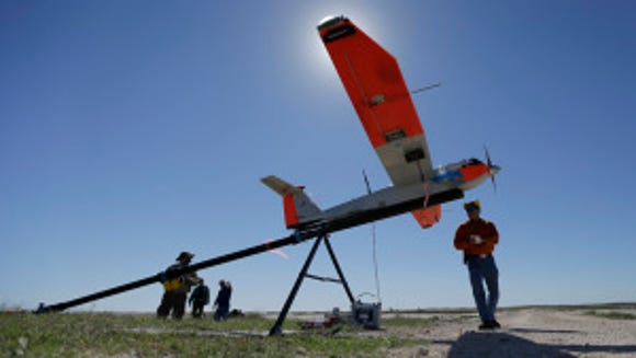 Crew chief Jack Edward Esparza, right, helps prepare an unmanned aircraft system for testing at a ranch near Sarita, Texas,  Jan. 15, 2014. A Texas A&M Corpus Christi research team is conducting tests to help  determine how drones can be integrated into existing airspace. (AP Photo/Eric Gay