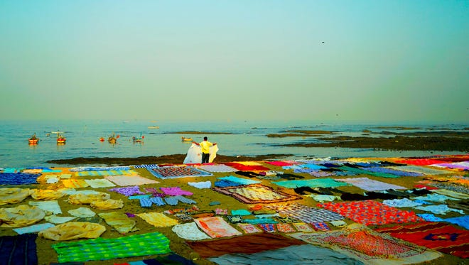 Colorful clothing and linens are set out to dry in Mumbai, India.
