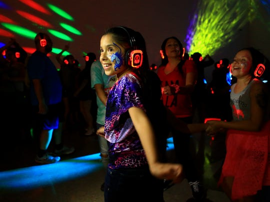 A girl dances and sings along to music from Selena at the Silent Disco during the first day of Fiesta de la Flor festival Friday, May 6, 2016, in Corpus Christi.