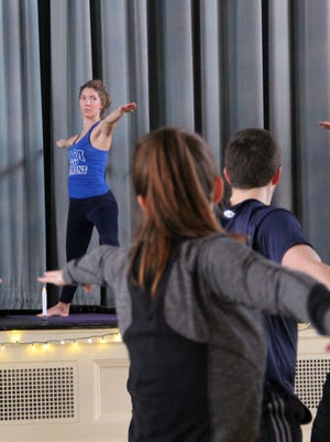 Allie Harris, 23, of Essex, stands on the stage of Contois Auditorium in Burlington's City Hall and leads a group in yoga on Sunday, Dec. 11, 2016. Harris organized the class to honor those affected by a crash in October that killed five teenagers.