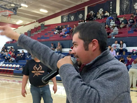 Auctioneer and DHS alumni Raul Perea accepts bids during