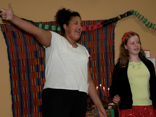 Evelyn Monje of Winooski and Clara Cichoskikelly of Hinesburg lead the crowd in Harambe to end the Kwanzaa Ceremony at The Schoolhouse in South Burlington.