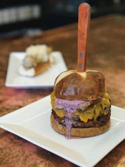 The Schatzi's burger on a pretzel roll with potato pancake, 1/2 lb patty, house cured pork belly and purple Schatzi's sauce at Schatzi's Pub and Bier Garden on Main Street in Poughkeepsie, April 4, 2017.