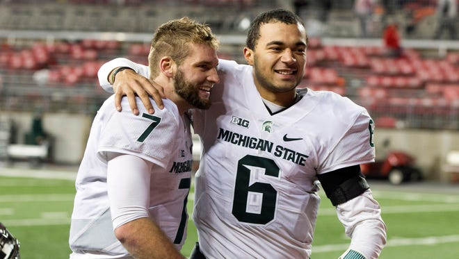 Michigan State quarterbacks Tyler O'Connor (7) and Damion Terry (6) celebrate after defeating the Ohio State Buckeyes, 17-14.