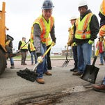 Gov. Rick Snyder, left, helps MDOT workers along Michigan Avenue near Trumbull patch potholes Thursday, April 23, 2015, in Detroit.