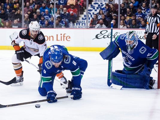 Vancouver Canucks defenseman Christopher Tanev (8) gets the puck away from Anaheim Ducks left wing Andrew Cogliano (7) as Canucks goaltender Anders Nilsson (31) watches during the first period of an NHL hockey game Tuesday, Jan. 2, 2018, in Vancouver, British Columbia. (Jonathan Hayward/The Canadian Press via AP)