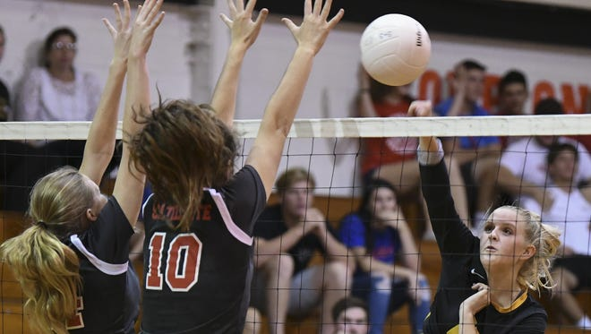 Bobbie Jo Schwantz of Merritt Island spikes past the guard of Satellite's Taylor Askeland (14) and Lindsey Morrison (10) during Thursday's 14-6A volleyball championship game.