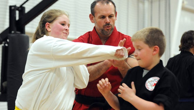 Sensei Brad Seward instructs Mackenzie Junke, 13, and Wyatt Williams, 9, on their technique in his Coszacks Elite Defense System class at the Tri-Valley Fitness Center in Dresden. Seward's dojo was inducted into the U.S. Martial Arts Hall of Fame for Leading System of the Year.