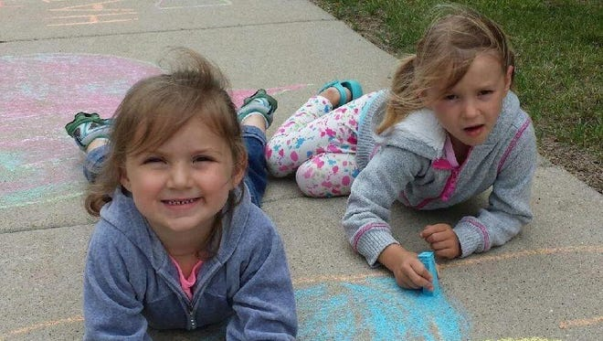 Libby Gessner, 3, left, and Diem Wagner, 4, are busy designing their sidewalk chalk creations on the pavement in front of the Lutheran Home.