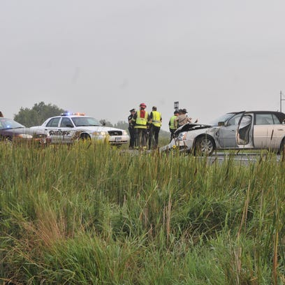 Investigators examine the scene of a fatal accident Monday morning at U.S. Highway 10 and Minnesota Boulevard. The Cadillac sitting across both lanes of eastbound Highway 10 struck an almost invisible Ford Taurus as the Ford attempted a turn from Minnesota Boulevard.
