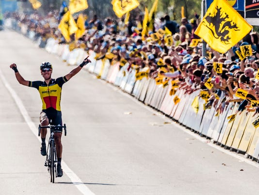 Belgium's Philippe Gilbert of the Quick-Step team celebrates as he crosses the finish line to win the Tour of Flanders cycling classic in Oudenaarde, Belgium on Sunday April 2, 2017. Greg Van Avermaet of the BMC Racing team finished second and Niki Terpstra of the Quick-Step team finished third. (AP Photo/Geert Vanden Wijngaert)