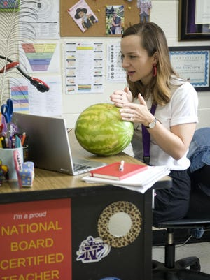 Zoe Faircloth, who teaches junior English at North Henderson High, uses a watermelon to explain a writing concept to her students on Aug. 28 in her classroom during virtual instruction.