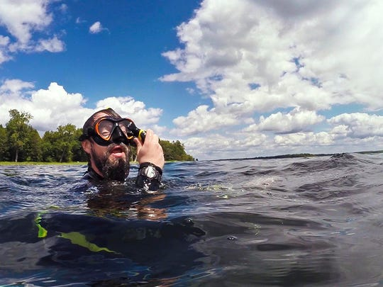 """Ben Maddox searches for fish to video record while snorkeling near Woods Island off of Hathaway Point in St. Albans on July 17. Maddox combines his video footage with his music for a video series called """"I See Fish People"""" that he posts on YouTube."""