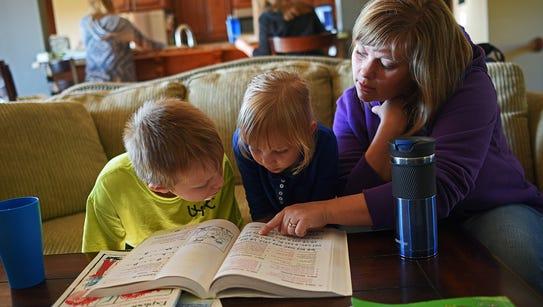 Kristin Brunick, helps two of her kids, Josiah, 8,