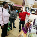 Salesman Juvani Levi shows pillows to Alvina Holman, left, and her twin sister, Alveda Gaines, at a kiosk in the Stones River Mall on Black Friday 2014. The sisters were Christmas shopping for their children.