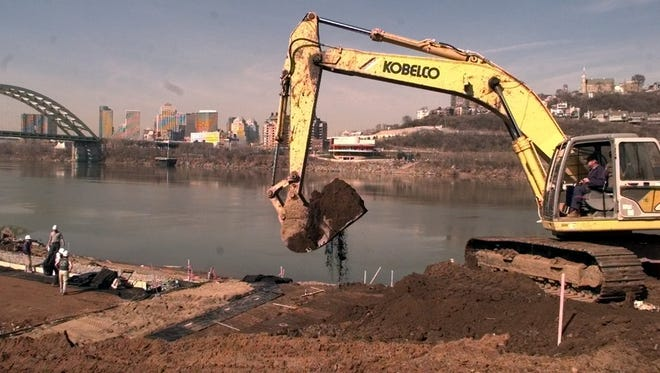 Bill Sparks (right), of Sunesis Construction Co., uses a track hoe to excavate along the Bellevue riverfront as workers begin to build a wire-face retaining wall for the Port Bellevue project, a restaurant-office complex.