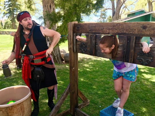 Kapriese Woita, 8, is soaked with water by Stacy Moore, a pirate actor with the Pirates of Reno.