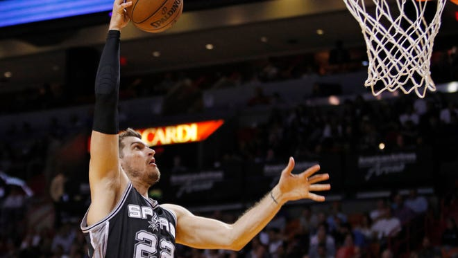 San Antonio Spurs center Tiago Splitter (22) goes high to dunk the ball against the Miami Heat in the first half of an NBA basketball game, Tuesday, March 31, 2015, in Miami. (AP Photo/Joe Skipper)